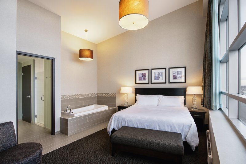Holiday Inn Saskatoon Downtown-Luxurious penthouse bedroom with soaker tub and oversized windows<br/>Image from Leonardo